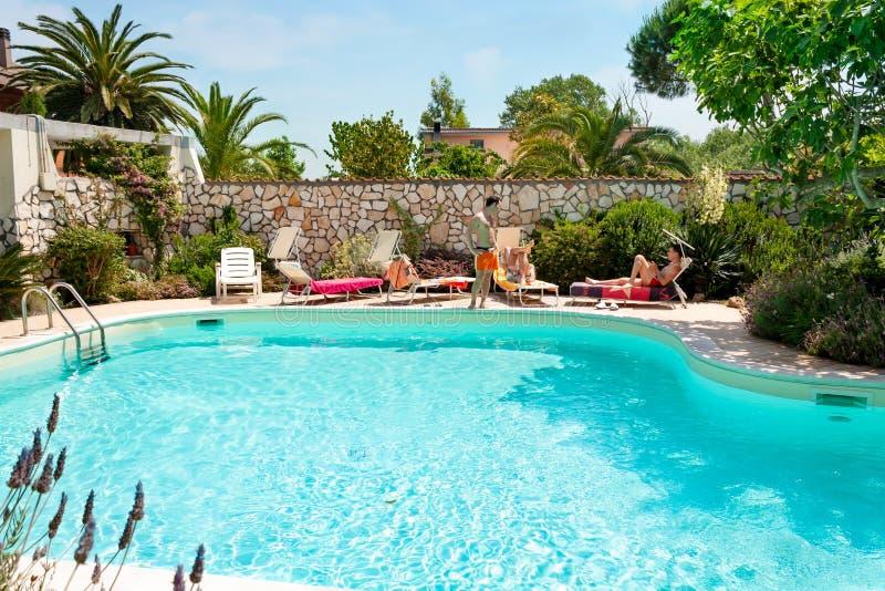 Men sunbathing beside the swimming pool royalty free stock photos