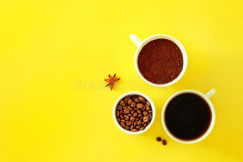 Three ceramic white cups with various coffee on a yellow background royalty free stock images