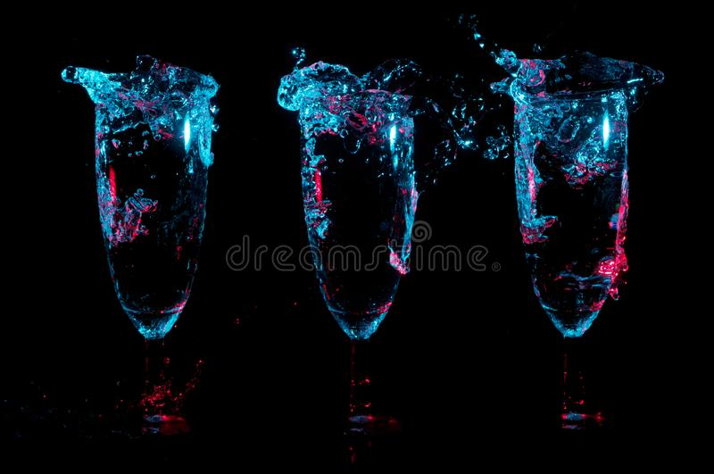 Three champagne flutes with big splashes under blue lights with red highlights on a black background royalty free stock images