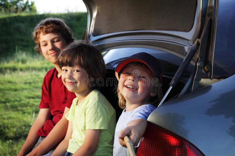 Three cheerful child sitting in the trunk of a car royalty free stock images