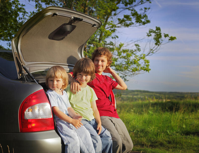 Three cheerful child sitting in the trunk of a car stock photos