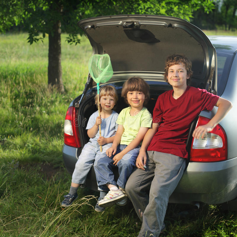 Three cheerful child sitting in the trunk of a car stock photo