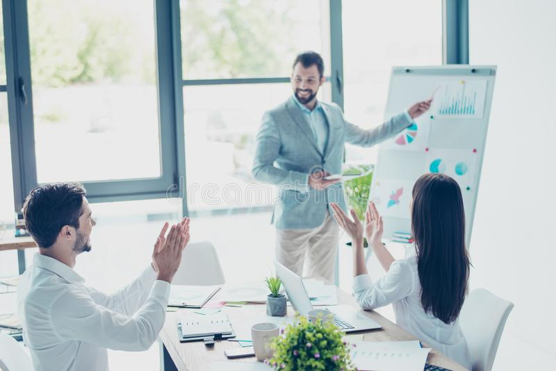 Three cheerful entrepreneurs are concentrated on data at the. Flipchart, it says the profit grew up, colleagues are clapping hands, celebrating, all are well royalty free stock photo