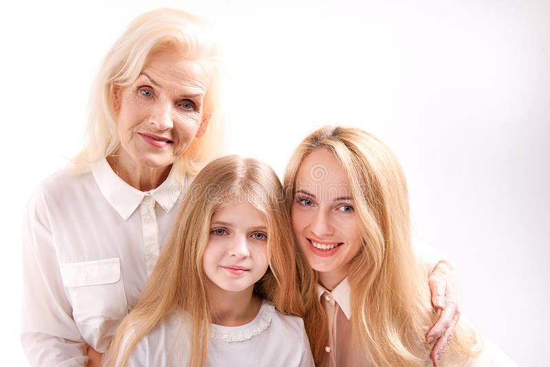 Three cheerful female persons looking at camera. Family idyll. Young girl is standing between mother and grandmother. They are brightly smiling stock photos
