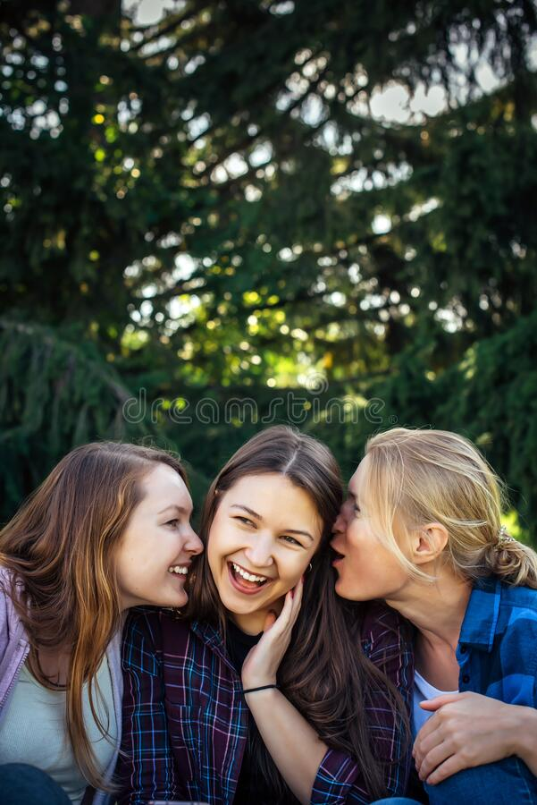 Three cheerful girls whisper and gossip against green foliage in the park. Women joke and laugh, vertical image stock images