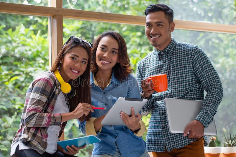 Three cheerful young employees working together on a project. Three cheerful young employees looking at a tablet PC while working together on a challenging stock images
