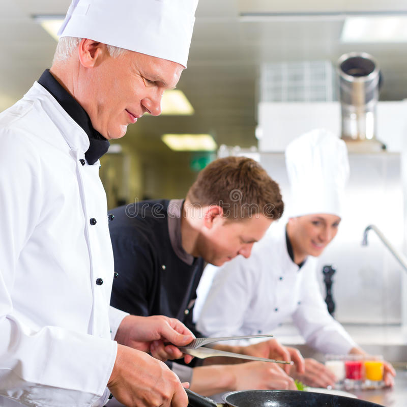 Three chefs in team in hotel or restaurant kitchen. Three chefs - men and woman - in hotel or restaurant kitchen working and cooking in team stock photos