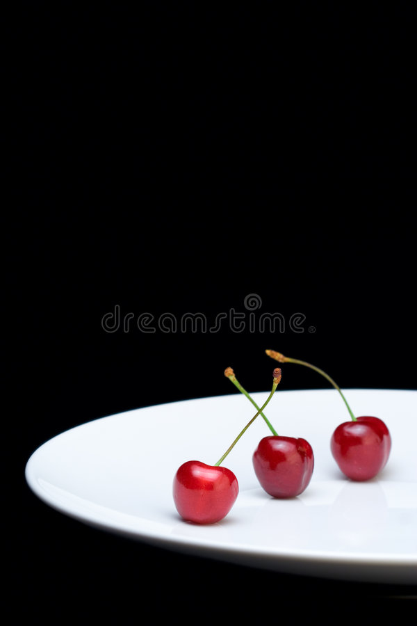 Three cherries on a plate royalty free stock images