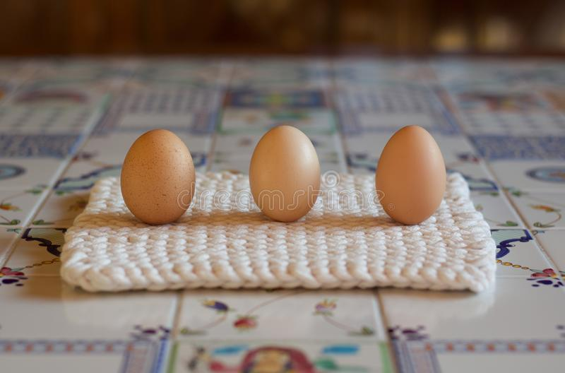 Three chichen eggs on a decorated ceramic table stock photo