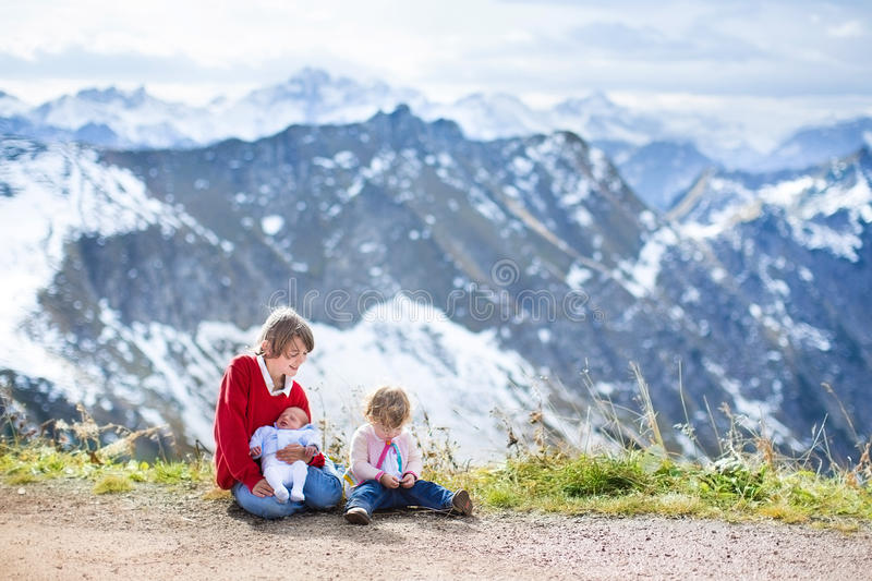 Three Children In Beautiful Snow Covered Mountains Stock Photo