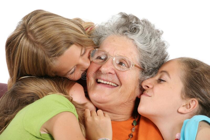 Three children kiss their grandmother on white background. Three blond haired children kiss their smiling grandmother on white background royalty free stock photography