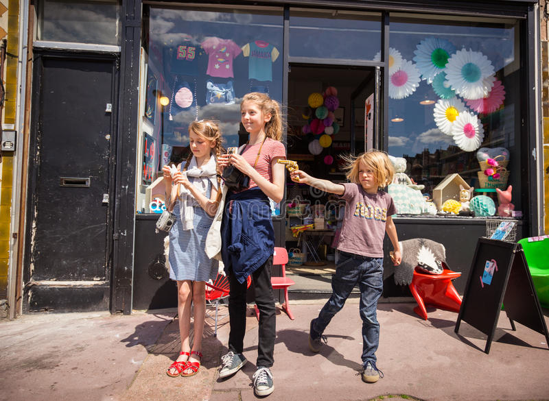 Three children outside a London toy shop, a little boy draws a toy gun royalty free stock photos