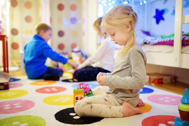 Three children playing with colorful plastic blocks at kids room. Cute girl playing at home or daycare. stock images