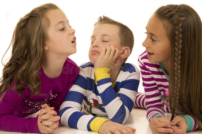 Three children playing laying down with silly expressions royalty free stock photo