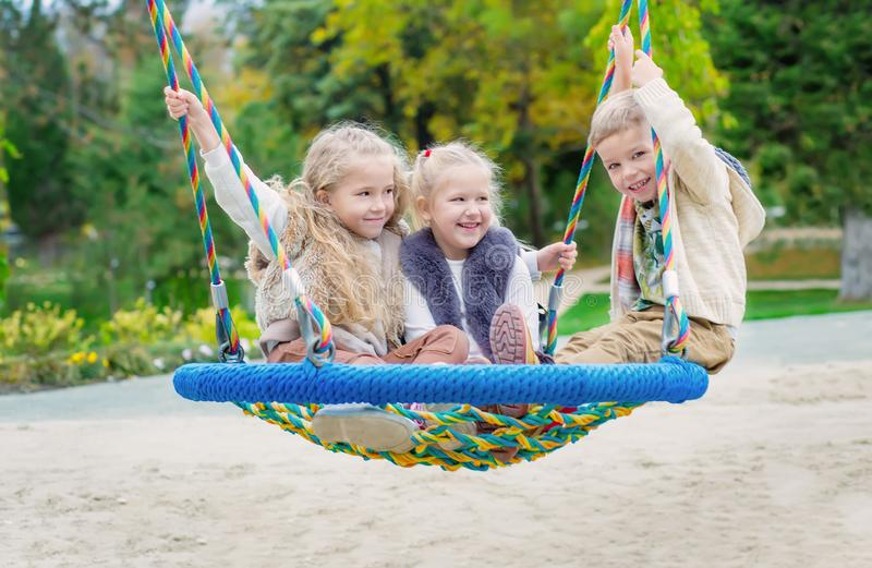 Three children playing in the park stock image