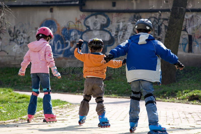 Three Children Roller Blading. Three Young Children roller blade away. Their backsides are in full length view. Setting is urban park with graffiti on walls royalty free stock photography