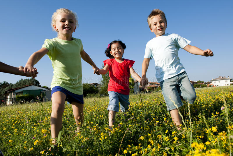Three children running holding hands royalty free stock image