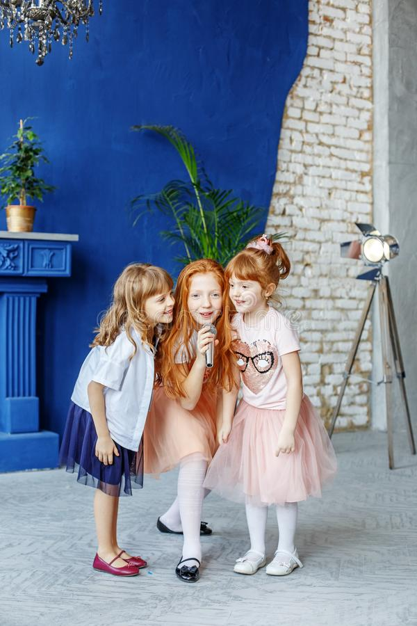 Three children sing a song in a microphone. Group. The concept i. S childhood, lifestyle, music, singing, friendship stock photo