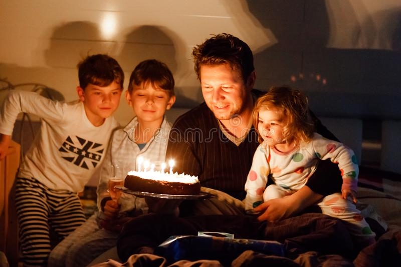 Three children, toddler girl and two school kids boys congratulating father to his birthday. Baby sister child, two. Brothers and dad with cake blowing candles royalty free stock photography