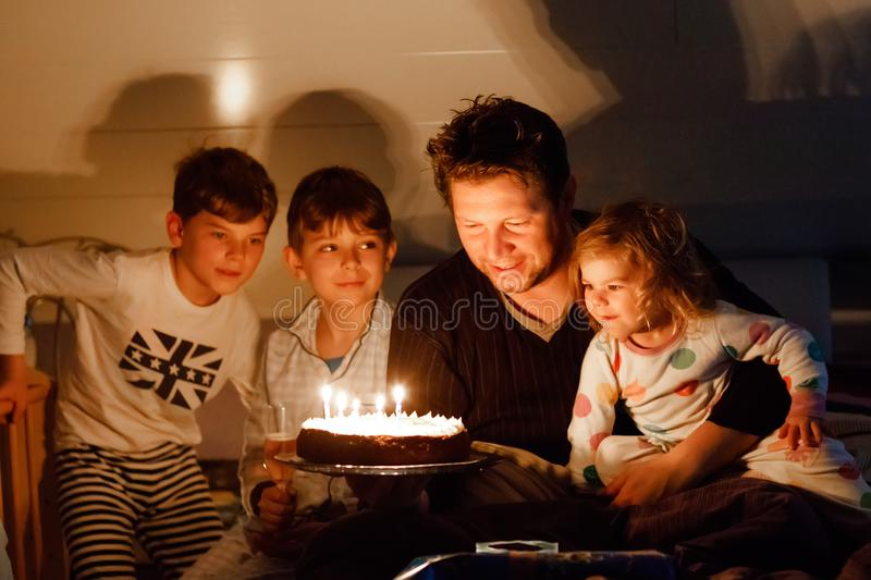 Three children, toddler girl and two school kids boys congratulating father to his birthday. Baby sister child, two. Brothers and dad with cake blowing candles stock images