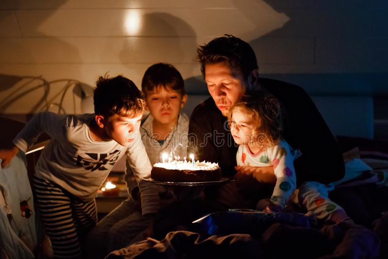 Three children, toddler girl and two school kids boys congratulating father to his birthday. Baby sister child, two. Brothers and dad with cake blowing candles royalty free stock photos