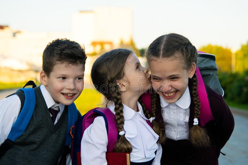 Three children whisper each other in the ear, after school lessons royalty free stock photo