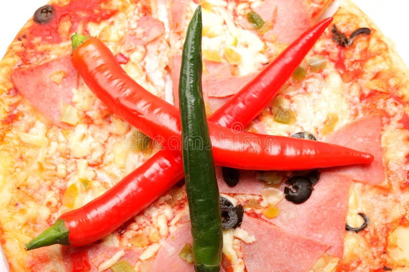 Three chili peppers on pizza stock photos