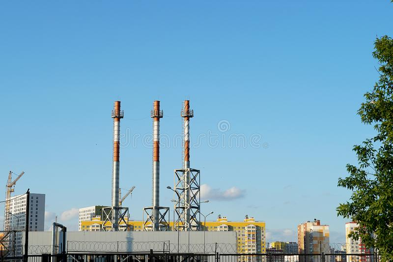 Three chimneys against a blue sky, without smoke. White and red pipes of the heating center in the city stock images