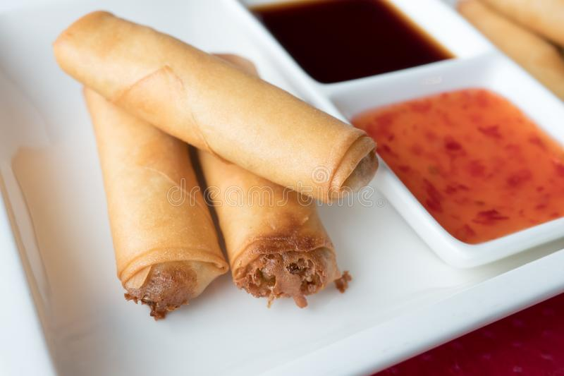 Three Chinese pancakes stuffed on a white plate with sweet chili sauce. Shallow depth of field royalty free stock photos