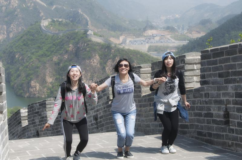 Three chinese woman having fun on the great wall of china royalty free stock image