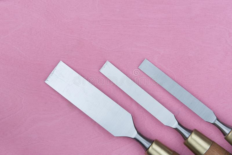 Three chisels on a pink background. Professional chisels on a pink wood background. Visible wood grain stock photos