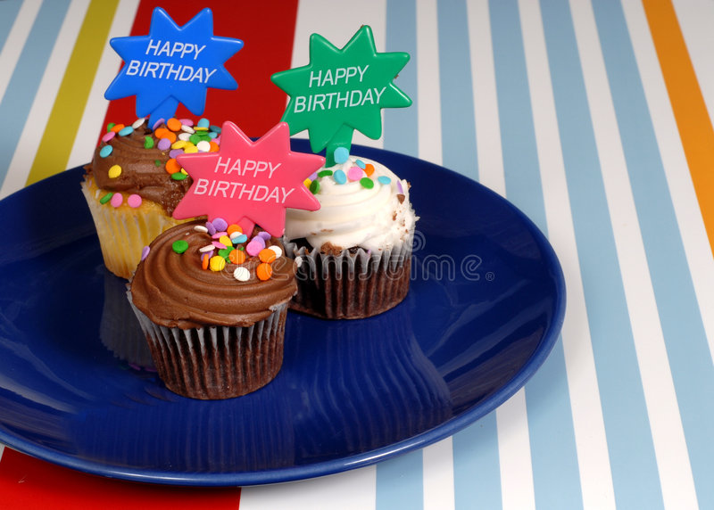 Three chocolate frosted cupcakes on a blue plate with stock photography