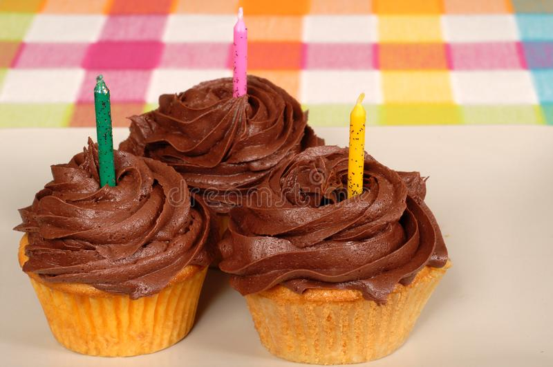 Three chocolate frosted cupcakes with candles royalty free stock photos