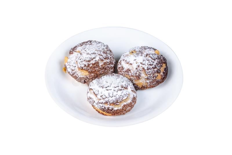 Three choux cakes with sugar powder on top on a white plate isolated on white background.  royalty free stock photo