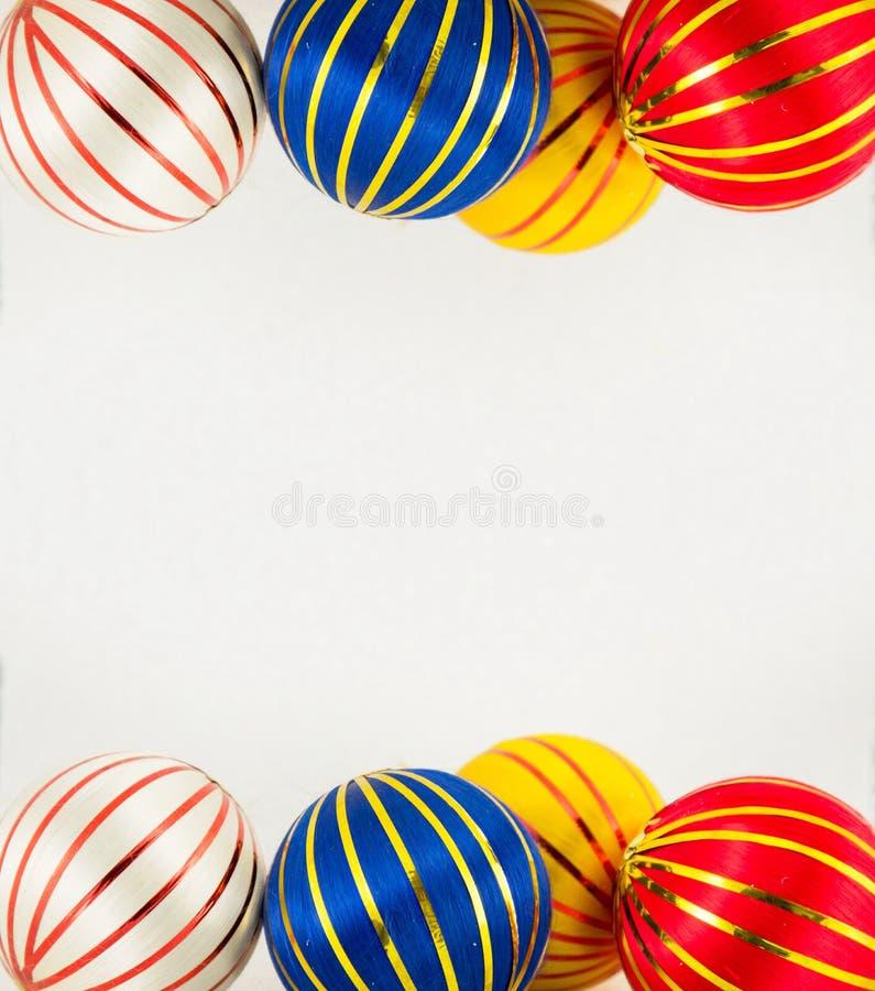 Three christmas balls on white. Three colorful christmas balls with gold lines on white royalty free stock photos