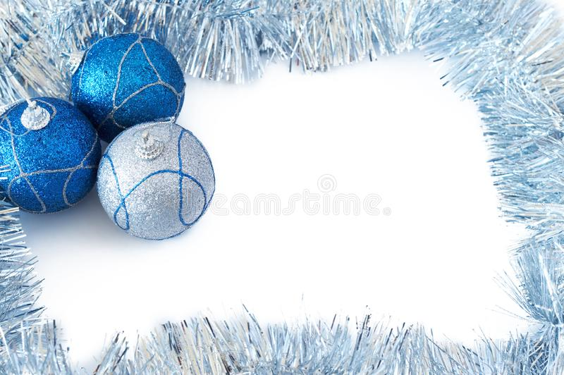 Three Christmas baubles with silver tinsel stock photography