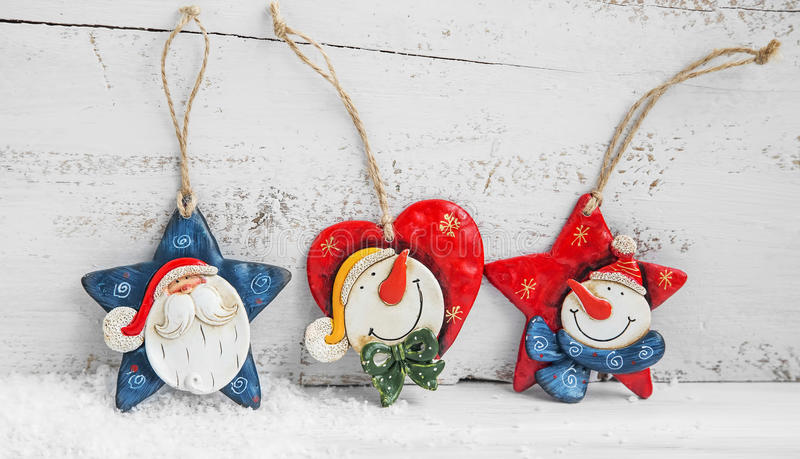 Three Christmas Decorations with Santa and Snowmans on Wooden Ba. Three Christmas Decorations with Santa and Snowmans on Painted Wood Background royalty free stock image