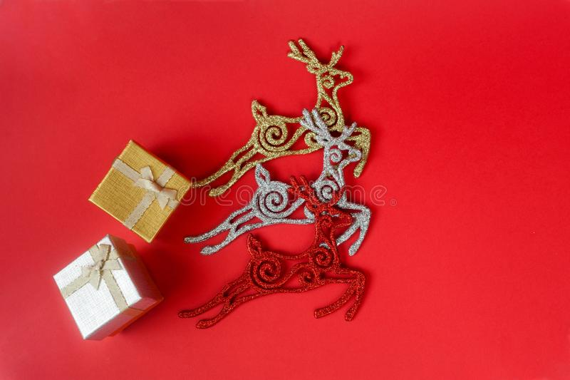 Three Christmas deers carry gifts. Three shiny Christmas deers carry 2 gift boxes with gifts and bows royalty free stock photos