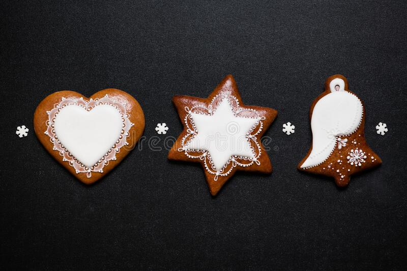 Three Christmas gingerbread cookies on black background stock photos