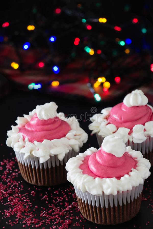 Three Christmas homemade chocolate cupcake with pink cream cheese frosting. Blur light and dark background. Selective focus stock images
