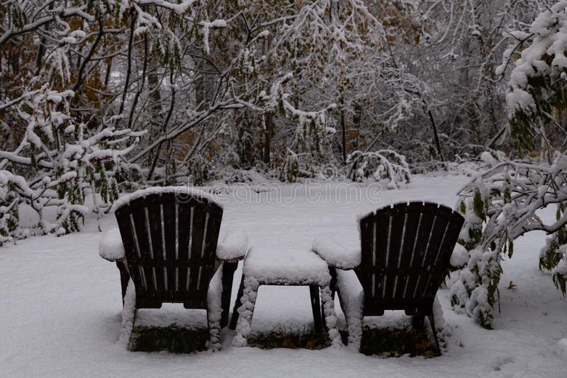 Early unexpected snowfall. Two brown lawn chairs and a table in a clearing in the woods covered in snow during an unexpected October snowfall in New Brunswick stock photo