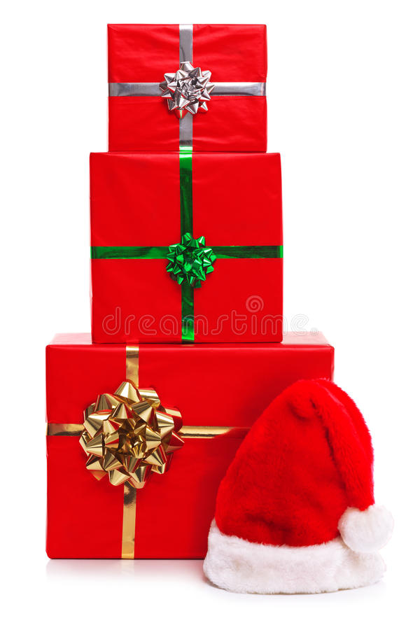 Three Christmas presents and Santa Claus hat. stock photo