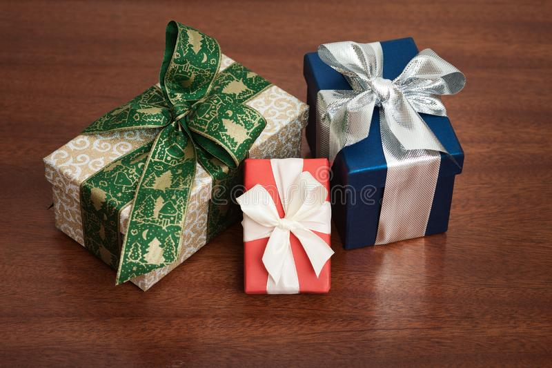 Three Christmas presents on a wooden background. stock image