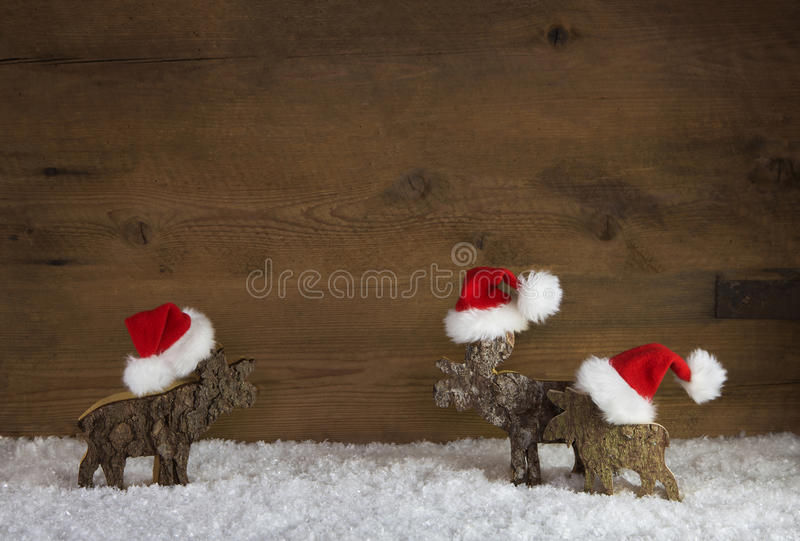 Three christmas reindeer of handmade wood with red white santa h royalty free stock photos