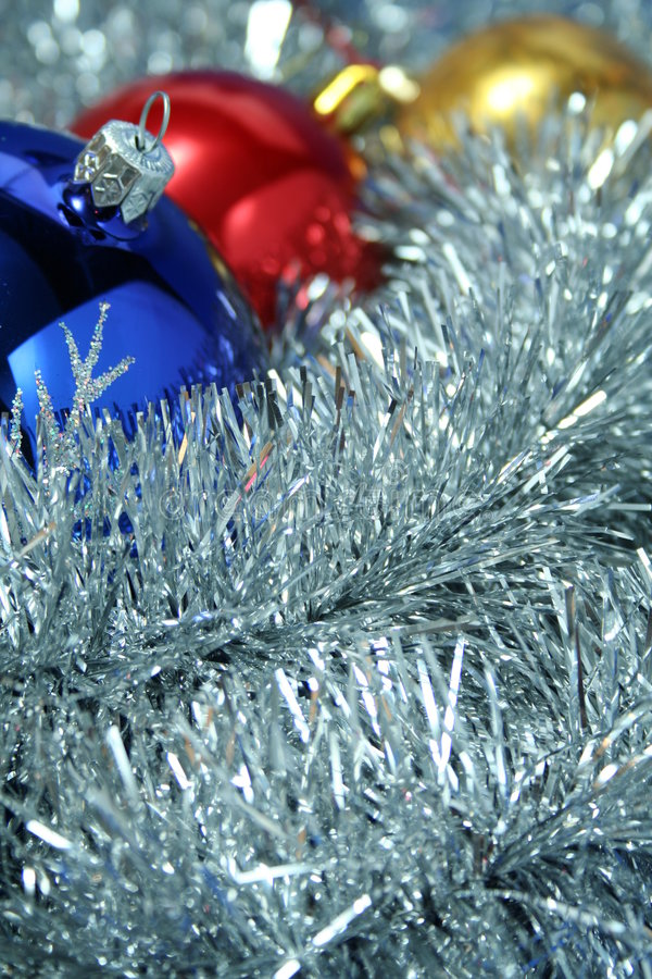 Three christmas sparkling spheres on a tinsel. Three christmas sparkling spheres of dark blue, yellow and red color on a background of a silvery New Year's stock image