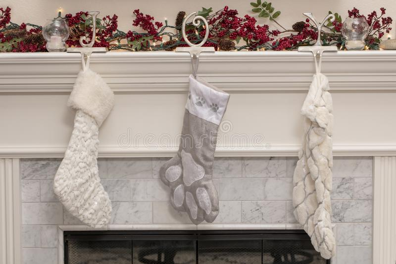 Three Christmas Stockings on a Fireplace Mantel. White Christmas stockings hanging from a fireplace mantel with green and red garland, and lights above royalty free stock photo
