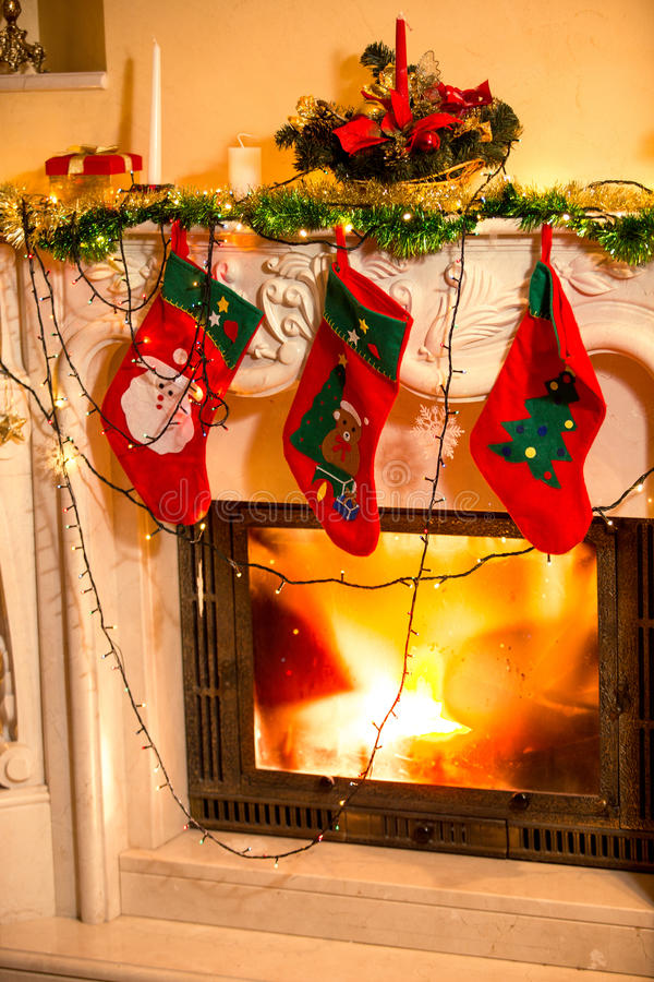 Three Christmas stockings hanging on decorated fireplace stock photography