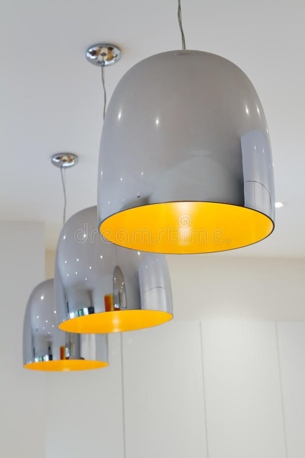 Three chrome and yellow contemporary kitchen pendant lighting. Three chrome and yellow contemporary kitchen pendant task lighting stock photo