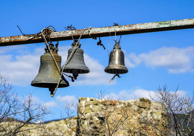 Three church bells of small, medium and large size hanging in chains against a blue sky whit white clouds. Georgia stock photos