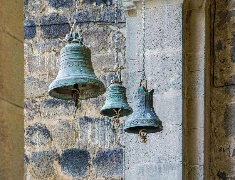 Three church bells of small, medium and large size hanging in chains. Vardzia, Georgia royalty free stock images